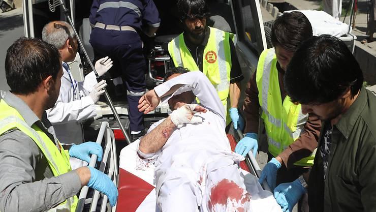 Afghanische Rettungskräfte bringen nach einem Autobombenanschlag einen Verletzten in einen Krankenwagen.