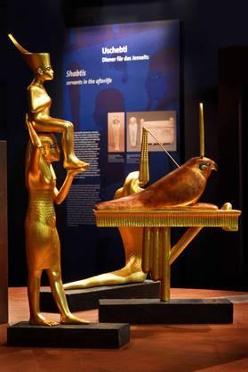 Götterfiguren, deren Symbolik auf Tafeln erklärt wird.