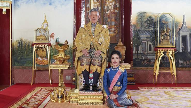 HANDOUT - ARCHIV - König Maha Vajiralongkorn von Thailand sitz auf seinem Thron, während neben ihm Sineenat Wongvajirapakdi kniet. Vajiralongkorn hat seiner im vergangenen Herbst verstoßenen offiziellen Geliebten alle königlichen und militärischen Titel wiederverliehen. Foto: Thailand Royal Office/AP/dpa - ACHTUNG: Nur zur redaktionellen Verwendung im Zusammenhang mit der aktuellen Berichterstattung und nur mit vollständiger Nennung des vorstehenden Credits