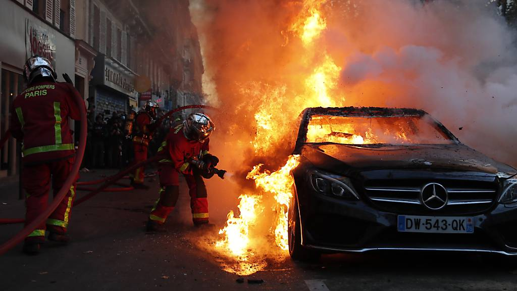 Die Feuerwehr löscht ein brennendes Auto in Paris. Foto: Francois Mori/AP/dpa