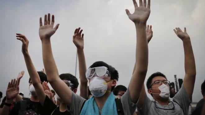 Demonstranten strecken die Arme in die Höhe und schützen sich mit Masken vor den Pfeffersprays der Polizei:Strassenszene am Donnerstag in Hongkong. Foto: Keystone - Wong Maye-E