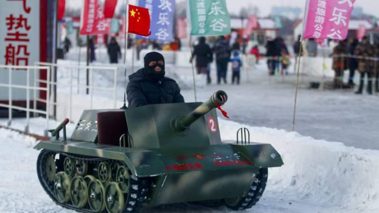 Chinas Panzer sind zu klein. Im Bild: Ein Mann fährt mit einem Spielzeugpanzer am Internationalen Schnee- und Eisfestival in Harbin. (Symbolbild)