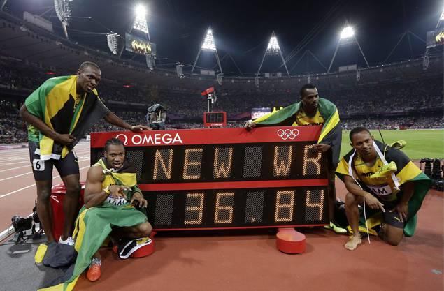 Von links, die Jamaikaner Usain Bolt, Yohan Blake, Nesta Carter und Michael Frater holen sich Gold und laufen einen neuen Weltrekord