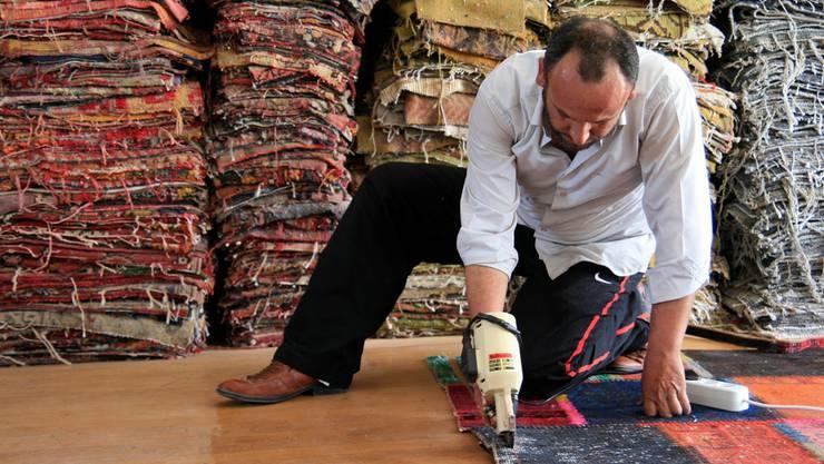 Da stockt einem der Atem: Mit einem elektrischen Messer werden Teppiche zerschnitten und auch die Ränder der neuen Patchworks getrimmt..