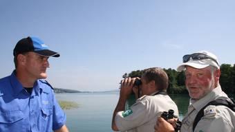 Der Feldstecher ist ihr wichtigstes Arbeitswerkzeug: Chefranger Bruno Fürst (Zweiter von links) mit Ranger Jörg Hiltbrunner und Mark Eberling von der Regionalpolizei aargauSüd bei ihrer Patrouille an der Schiffanlegestelle Seengen.