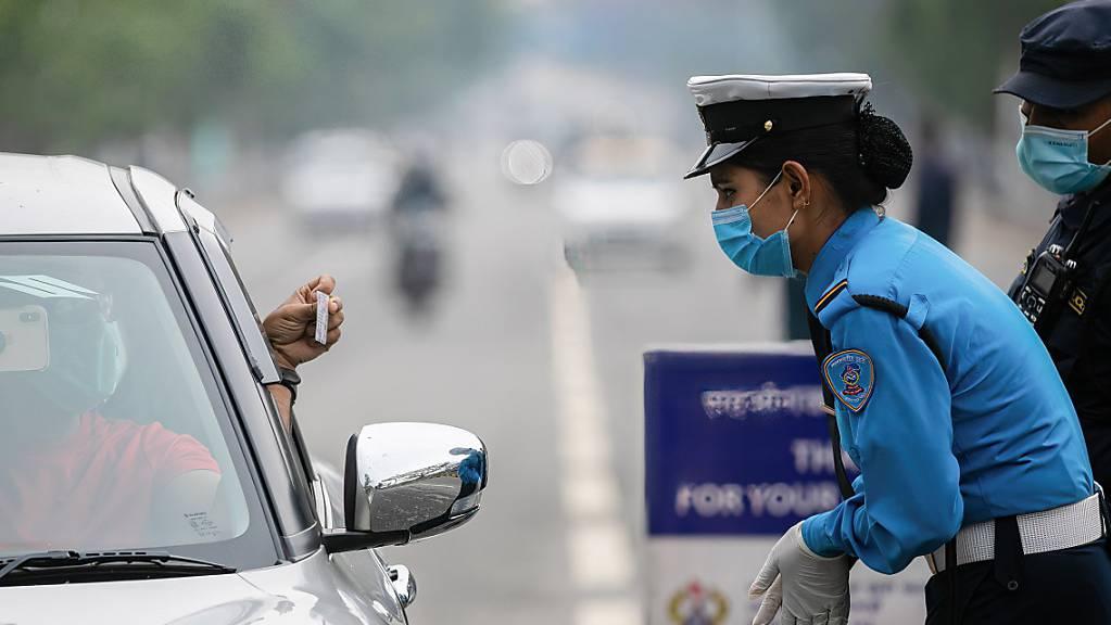 Polizisten kontrollieren die Fahrzeugpapiere am vierten Tag des landesweiten Lockdowns. Angesichts rasch steigender Corona-Fallzahlen streicht Nepal Flugverbindungen für rund zwei Wochen.