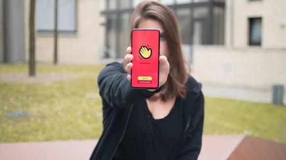 Auflösung zum Teaserbild: Eine junge Frau hält ein Smartphone mit der Houseparty-App, die es ermöglicht, in Gruppen virtuelle Videopartys zu feiern.
