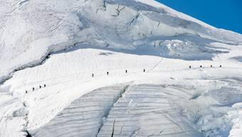 Bergsteiger traversieren den Feegletscher auf dem Weg auf das Allalinhorn oberhalb von Saas-Fee.