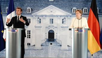 Bundeskanzlerin Angela Merkel und Frankreichs Präsident Emmanuel Macron sprechen nach ihrem Treffen im Schloss Meseberg in Brandenburg. Foto: Kay Nietfeld/dpa-Pool/dpa