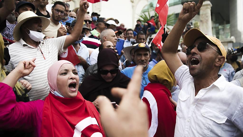 Demonstrierende skandieren Slogans während eines Protests gegen den Präsidenten Saied. Foto: Riadh Dridi/AP/dpa