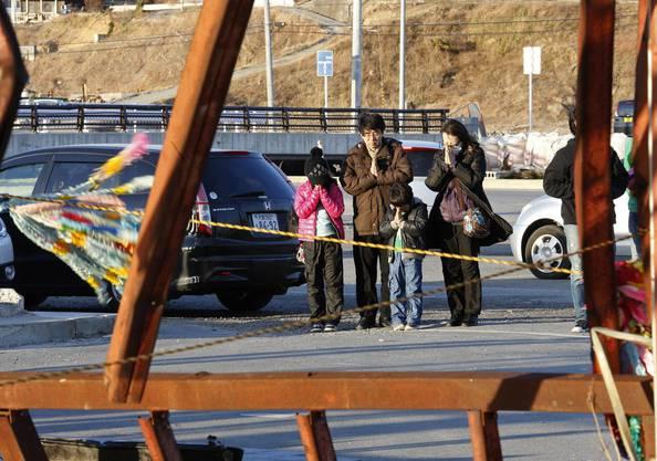 Eine japanische Familie hält Inne und gedenkt der Erdbebenopfer