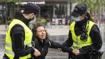 Polizisten verhaften eine demonstrierende Lockdown-Gegnerin auf dem Sechseläutenplatz in Zürich.