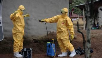 Ein Helfer desinfiziert in Liberia einen anderen Helfer (Archiv)