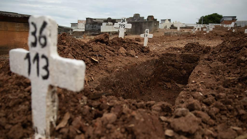 dpatopbilder - Ein einfaches Kreuz ohne Namen und mit einer Nummer steht an einem offenen Grab am Friedhof von Iraja. Foto: Fernando Souza/dpa