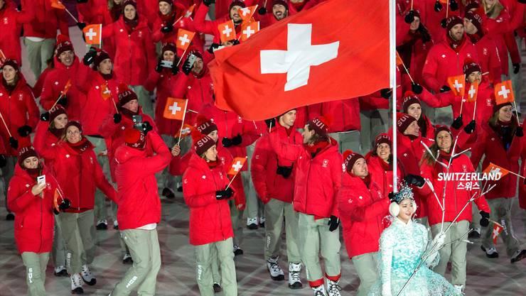 Faszination Eröffnungsfeier: Während Fahnenträger Dario Cologna voller Konzentration seinen Job erledigt, bleibt für das Schweizer Team Zeit, um zu geniessen und die Momente per Handy festzuhalten.