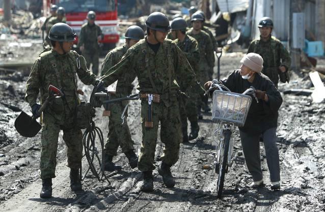 Soldaten fordern eine Frau in einer Hafenstadt auf, höheres Gebiet aufzusuchen, nachdem ein Helikopter am Montag eine Tsunamiwarnung herausgegeben hat. Die Warnung ist inzwischen aufgehoben worden.