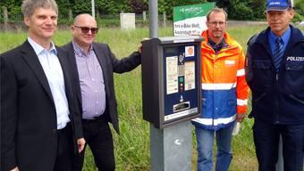 Eine der fünf umgerüsteten Handy-Parkuhren in Lenzburg mit von links André Cuttat und Tomy Eng von der Firma smarcom AG, Christian Brenner, Abteilungsleiter Tiefbau vom Lenzburger Stadtbauamt, und Markus Basler von der Regionalpolizei Lenzburg. tf