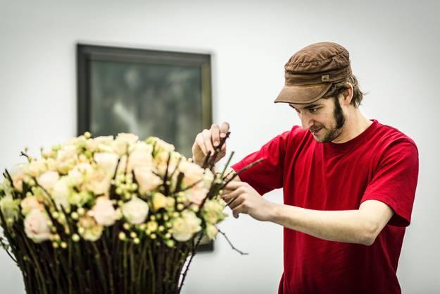 Andreas Geissmann muss aufpassen, dass er sich an den Dornen seines duftenden Rosengestecks nicht sticht.
