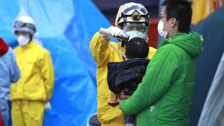 Ein Vater mit seinem Baby lässt seine Strahlung eruieren,