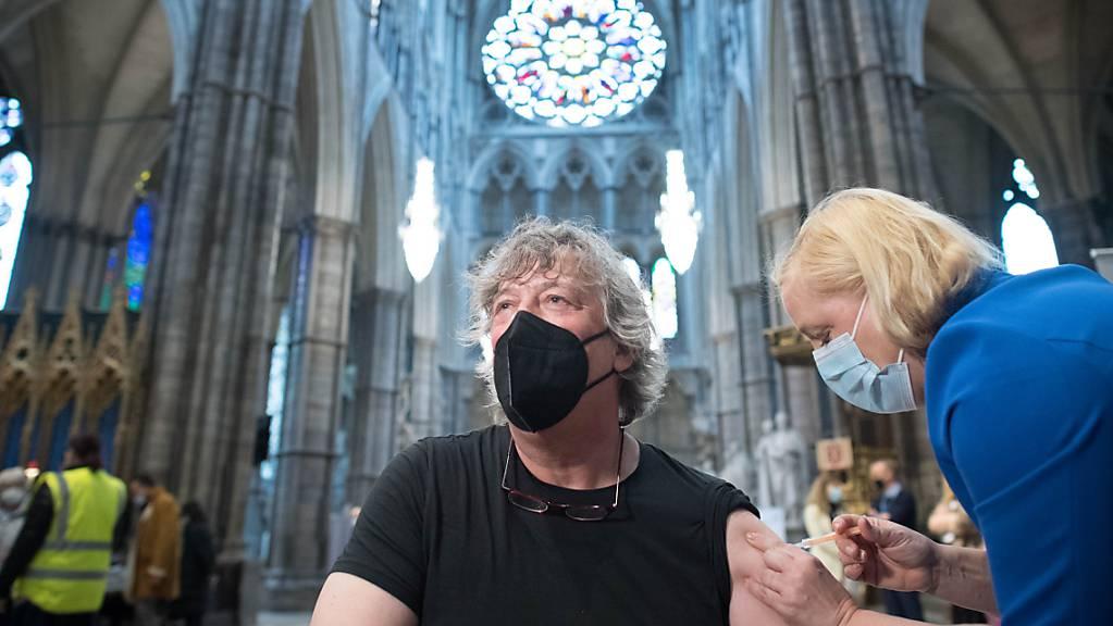 dpatopbilder - Stephen Fry, Schauspieler und Schriftsteller aus Großbritannien, wird in der Poets' Corner, einem Teil des Querschiffs der zu einer Impfstelle umfunktionierten Kirche Westminster Abbey, gegen Corona geimpft. Foto: Stefan Rousseau/PA Wire/dpa
