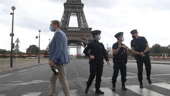 Französische Polizisten sichern das Gebiet um den Eiffelturm. Die Pariser Polizei hat nach einer Bombendrohung das Gebiet um den Eiffelturm evakuiert. Foto: Michel Euler/AP/dpa