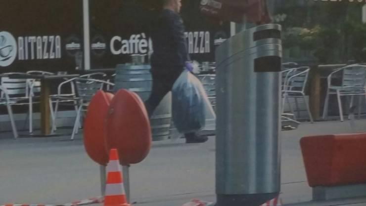 Polizeieinsatz am Bahnhof Aarau: Ein Beamter trägt den verdächtigen Koffer in einem Sack weg.