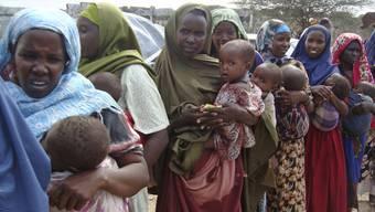 Somalische Frauen stehen mit ihren Kindern in einem Flüchtlingslager in Mogadishu Schlange bei der Essensausgabe (Archiv)