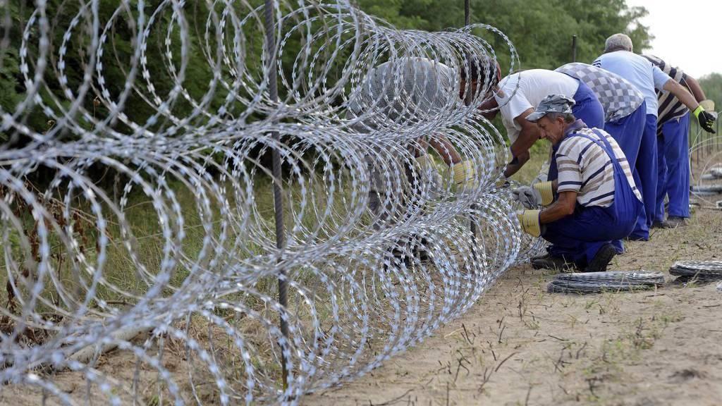 Ungarische Soldaten erstellen den 175 Kilometer langen Stacheldraht-Zaun um Flüchtlinge zu stoppen.