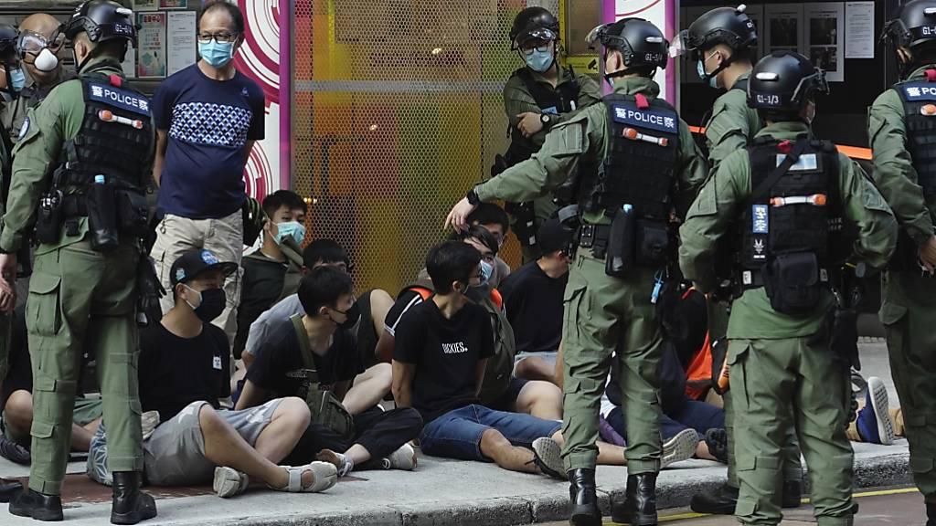 Polizisten nehmen Demonstranten (M) fest. Nach der umstrittenen Verschiebung der Wahl um ein Jahr hatte die Opposition in der chinesischen Sonderverwaltungszone für Sonntag zu Protesten aufgerufen. Foto: Vincent Yu/AP/dpa