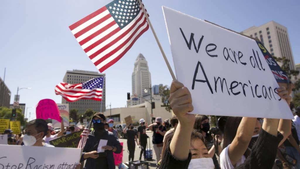 ARCHIV - Menschen nehmen an einer Kundgebung gegen Hassverbrechen gegen asiatische Amerikaner teil. (Archivbild) Foto: Damian Dovarganes/AP/dpa