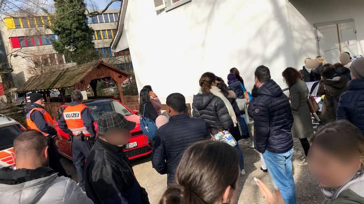 Eltern der Schülerinnen und Schüler versammeln sich beim Eltern-Treffpunkt, der von der Polizei eingerichtet wurde.