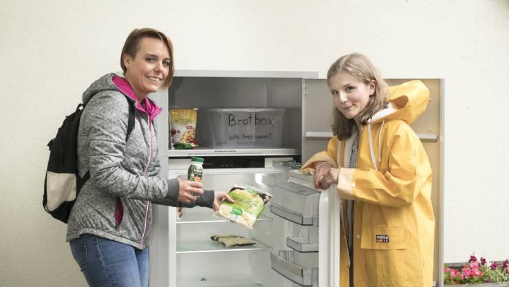 Samira Thomen (r.) hat den Gemeinschaftskühlschrank im Chrüzacher organisiert. Kerstin Schmidt hält ihn mit drei weiteren Freiwilligen in Stand