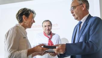 Chefköchin Bernadette Lisibach erhält ihre Auszeichnung von Bundesrat Guy Parmelin.