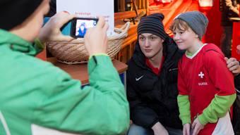 Dean Kukan posiert anlässlich eines Charity-Auftritts des Nationalteams in Chur mit einem jungen Fan für ein Foto.