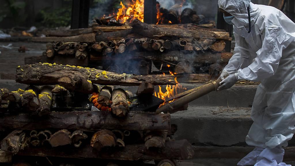 Ein Verwandter trägt einen Schutzanzug während der Einäscherung eines an Covid-19 Verstorbenen. In Indien sind nach offiziellen Zahlen mehr als 400 000 Menschen an oder mit Corona gestorben. Foto: Anupam Nath/AP/dpa