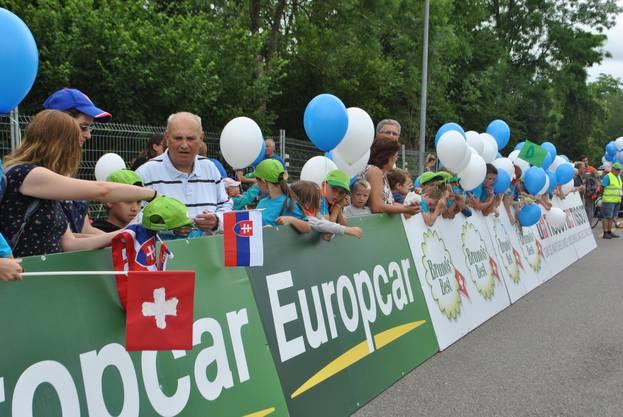 An der Strecke warten Fans mit Fahnen und Ballons auf den Start.