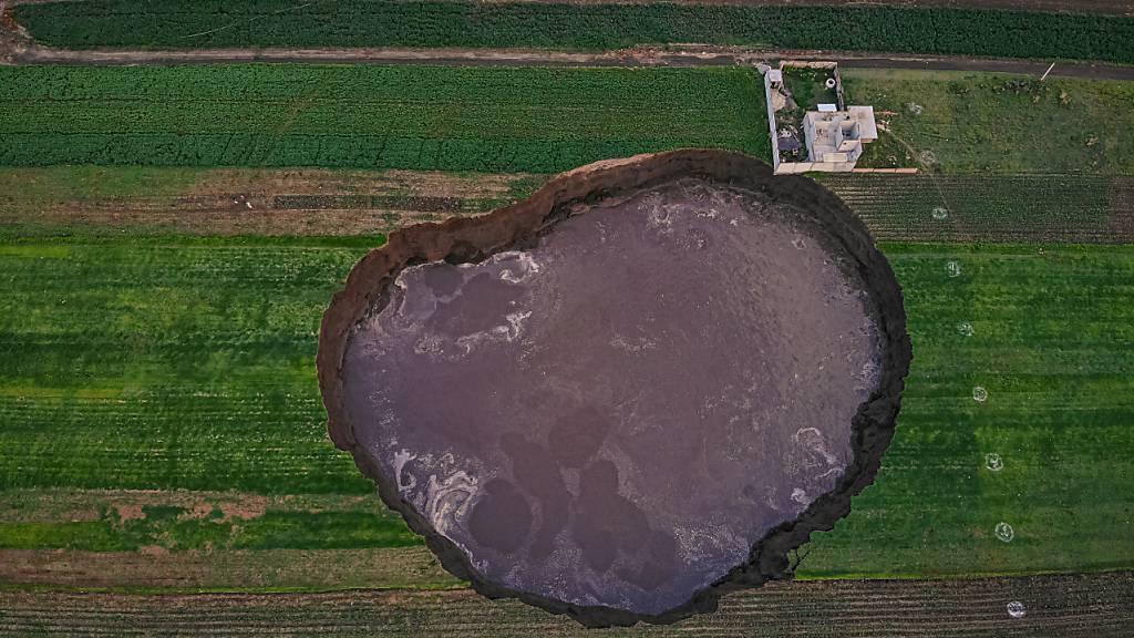 Aus der Vogelperspektive ist ein großer mit Wasser gefüllter Krater zu sehen. Foto: Karlos Pinpunk/dpa