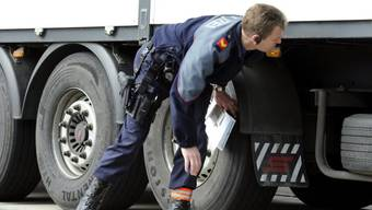 Ein Polizist kontrolliert einen Lastwagen anlässlich einer Car- und Schwerverkehrskontrolle der Kantonspolizei Zürich. (Archiv)
