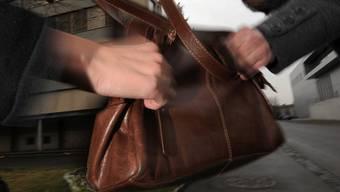 Ein Unbekannter entriss der 83-Jährigen die Handtasche, wobei sich die Frau leicht verletzte. (Symbolbild)