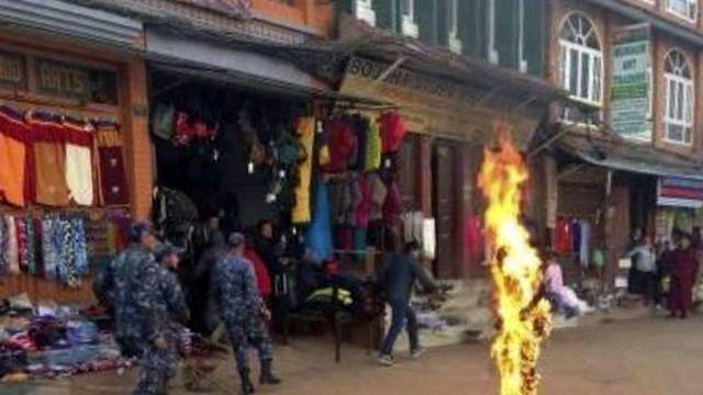 Chinesische Sicherheitskräfte eilen zum brennenden Mönch