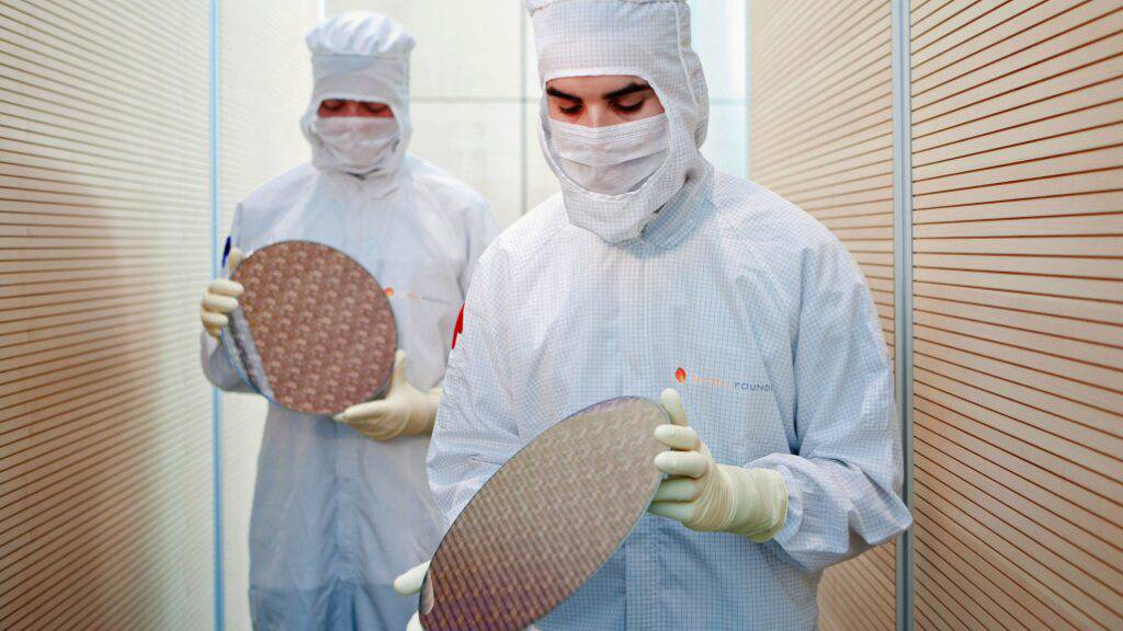 Die Chipbrance investiert derzeit massiv in neue Fabriken - im Bild Dresdner Globalfoundries-Arbeiter mit Chip-Wafern. (Archivbild)