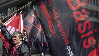 """Die Oppositionsgruppe """"Basis 21"""" nutzte die 1. Mai-Demonstration in Basel, um Kritik an der Unia-Leitung zu äussern. Rund 100 Personen schlossen sich der Gruppe an und stellten sich dem Demonstrationszug kurzzeitig in den Weg, um an der Mittleren Brücke ein Transparent zu befestigen."""