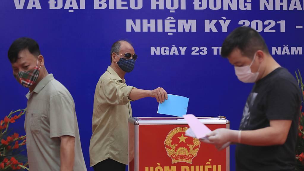 Menschen mit Mund-Nasen-Schutz stimmen bei der Wahl der Nationalversammlung in einem Wahllokal ab. Foto: Hau Dinh/AP/dpa