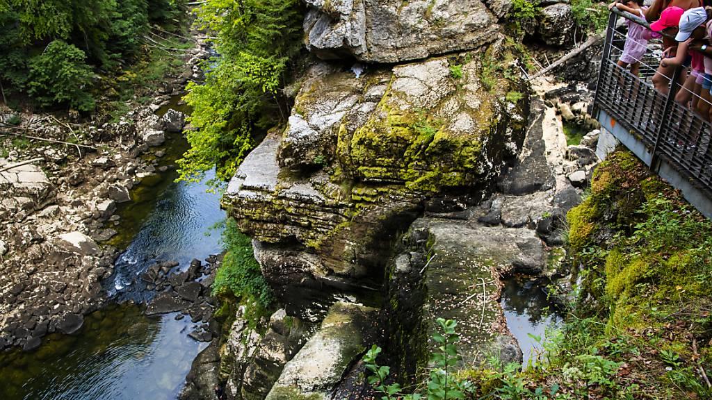 Der Saut-du-Doubs an der französisch-schweizerischen Grenze ist ausgetrocknet. Einige junge Leute sprangen am Mittwoch über die zugänglichen Steine in das darunter liegende Wasser.