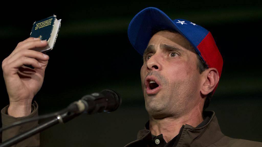 Henrique Capriles, Oppositionspolitiker in Venezuela, spricht zu seinen Anhängern und hält dabei eine Miniaturausgabe der Verfassung von Venezuela in die Höhe.