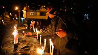 Mit Kerzen gegen den Krieg: Ein Soldat versucht, am Ort eines von den Farc-Rebellen verübten Attentats für versöhnliche Stimmung zu sorgen.