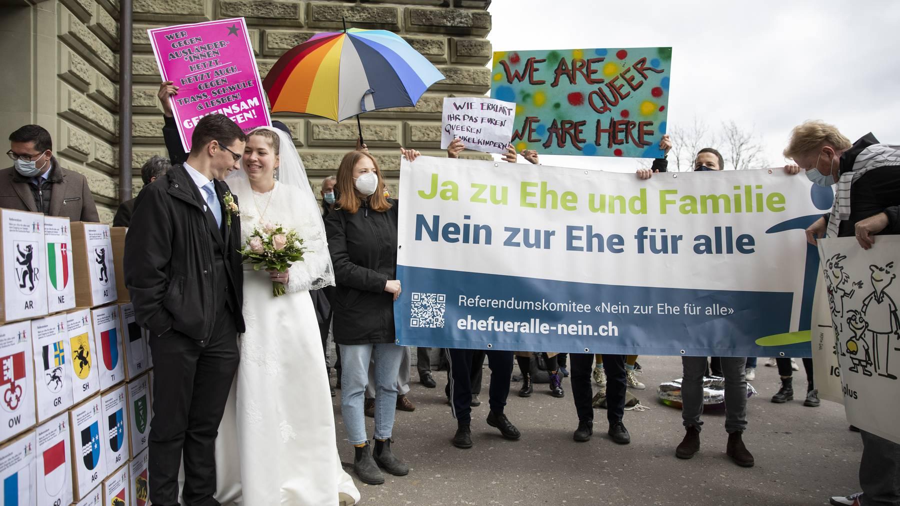 Demonstranten, hinten, protestieren bei der Einreichung der Unterschriften fuer das Referendum «Nein zur Ehe fuer alle», am Montag, 12. April 2021, in Bern.