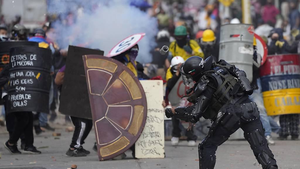 Ein Polizist wirft eine Blendgranate auf Demonstranten während anhaltender Anti-Regierungs-Proteste, die durch vorgeschlagene Steuererhöhungen auf öffentliche Dienstleistungen, Kraftstoff, Löhne und Renten in Bogota, Kolumbien, ausgelöst wurden. Foto: Fernando Vergara/AP/dpa