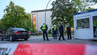 dpatopbilder - Mehrere Polizeibeamte und Zivilisten stehen im abgesperrten Bereich vor der Synagoge in Hamburg-Harvestehude. Foto: Jonas Walzberg/dpa