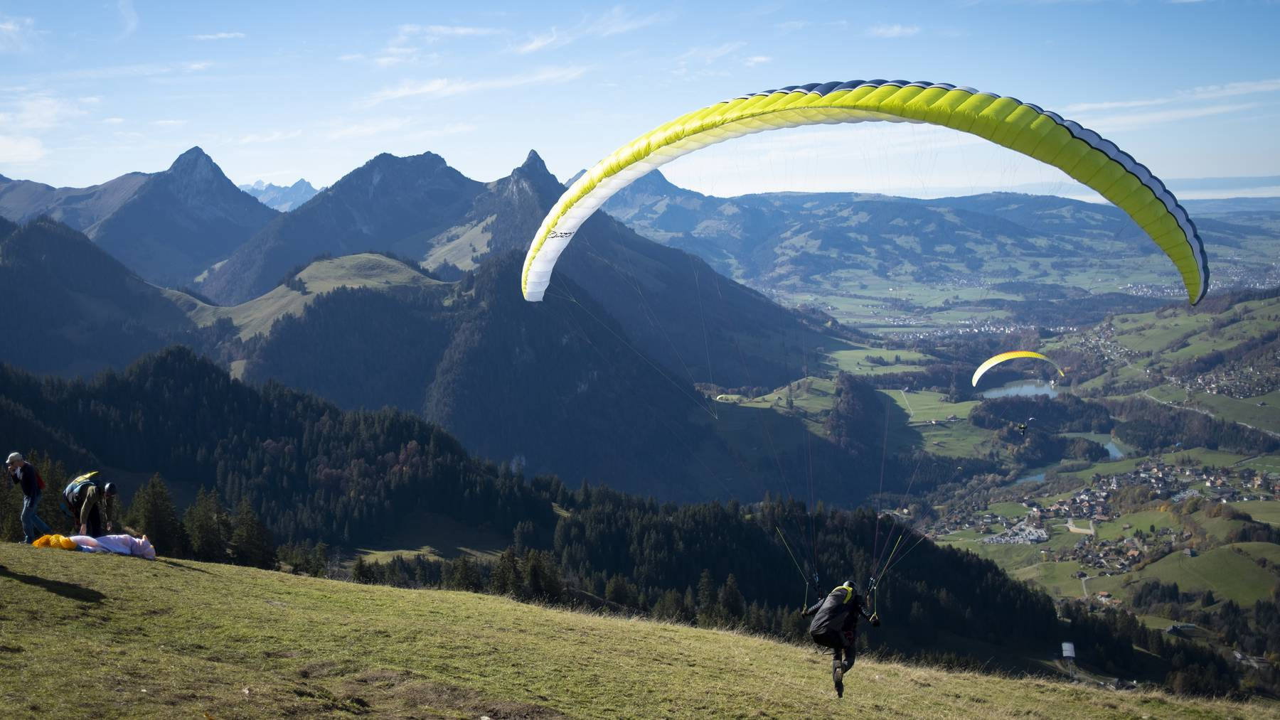 Tourists and paragliders enjoy a sunny autumn weather day in front of Swiss Alps mountains during the second wave pf the coronavirus disease (COVID-19) outbreak, in Charmey, Fribourg, Switzerland, Saturday, October 31, 2020.